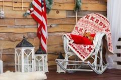 La mecedora con una manta y un juguete llevan, en las paredes de madera adornadas una bandera americana dentro Imagen de archivo