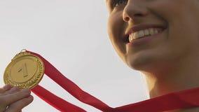 La medalla de oro de la deportista que se besa feliz y la sonrisa, ganador femenino disfrutan la victoria almacen de metraje de vídeo