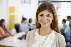 La mediados de mujer blanca adulta sonríe a la cámara en oficina abierta del plan imagen de archivo