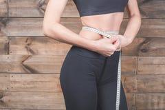 La medida atractiva de la muchacha la cintura, centímetros graba Imagenes de archivo