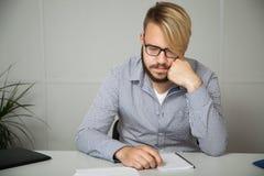 La mejilla cuidadosamente apoyada joven de la mano del hombre de negocios, refleja en el informe, sentándose en un escritorio en  Fotos de archivo