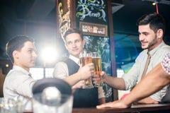 La mejor barra para una cerveza Cuatro hombres de los amigos que beben la cerveza y que tienen f Imagenes de archivo