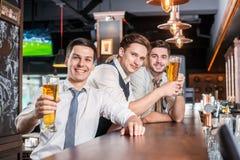 La mejor cerveza en la barra Cuatro hombres de los amigos que beben la cerveza y que la tienen Fotos de archivo libres de regalías