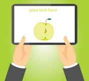 La mela a metà verde su una compressa ha tenuto in mani Fotografia Stock