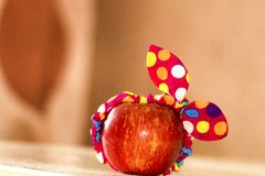 La mela rossa con un grande fondo, una mela sta trovandosi su una tavola, una mela in una fasciatura, una mela divertente, minima immagini stock