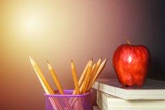 La mela rossa sul libro con il gessetto per lavagna e della matita imbarca come sedere Fotografia Stock Libera da Diritti