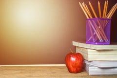 La mela rossa sul libro con il gessetto per lavagna e della matita imbarca come sedere Immagini Stock