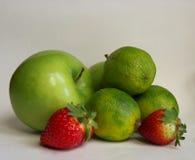 La mela verde con calce e le fragole con colore acceso contrappongono fotografia stock libera da diritti