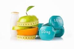 La mela verde con nastro adesivo di misurazione con un paio delle teste di legno blu di forma fisica e la proteina bevono Immagine Stock