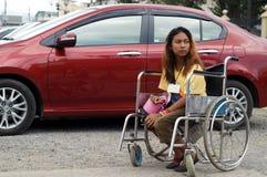 La mendiante de jeune dame sur le fauteuil roulant prie au parking d'église photographie stock libre de droits