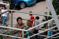 La mendicante del bambino e della madre sulla passerella alla giunzione attraversa fra Anawrahta Rd e Sule Pagoda Rd fotografie stock
