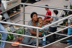 La mendicante del bambino e della madre sulla passerella alla giunzione attraversa fra Anawrahta Rd e Sule Pagoda Rd immagini stock libere da diritti