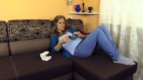 La mentira cansada de la mujer embarazada en el sofá mide su presión arterial metrajes