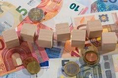 La mentira de billetes de banco con de madera corta monedas en cuadritos Imagenes de archivo