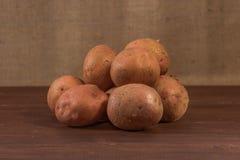 La mentira de las patatas crudas en la tabla Foto de archivo