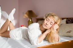 La mentira de relajación rubia sincera blanda atractiva de la mujer joven en la cama blanca en los rayos del sol o los ojos del h Fotos de archivo