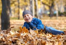 La mentira del muchacho en amarillo se va en el parque del otoño, día soleado brillante, hojas caidas en fondo Imagen de archivo libre de regalías
