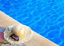 La mentira del sombrero de paja y de los vidrios de sol cerca a la piscina fotos de archivo