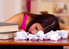 La mentira del top del rosa de la mujer que llevaba morena joven dobló sobre el escritorio con la pila de libros colocados en ell Foto de archivo
