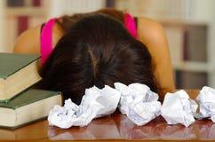 La mentira del top del rosa de la mujer que llevaba morena joven dobló sobre el escritorio con la pila de libros colocados en ell Imagen de archivo libre de regalías