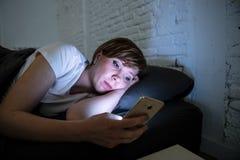 La mentira hermosa joven de la mujer agujereó en cama usando el teléfono elegante tarde en la noche en un dormitorio oscuro fotografía de archivo