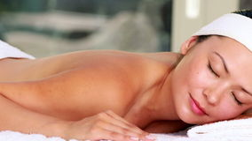 La mentira morena hermosa en la tabla del masaje con los ojos se cerró metrajes