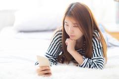 La mentira sonriente de la mujer asiática joven hermosa se relaja en la cama por la mañana Fotos de archivo