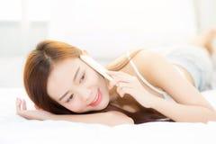 La mentira sonriente de la mujer asiática joven hermosa y se relaja en la cama por la mañana Fotografía de archivo libre de regalías