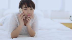 La mentira sonriente a relajarse en el dormitorio, muchacha de la mujer asiática joven hermosa usando hablar elegante móvil del t