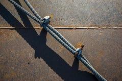La menzogne dei cavi metallici ha allungato con i morsetti di cavo metallico su un di piastra metallica saldato ed arrugginito co Fotografie Stock Libere da Diritti