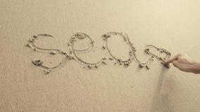 La MER avec le coeur écrit sur le sable de plage a lavé toujours par des vagues Images libres de droits
