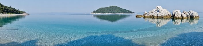 La mer bascule à calme et l'eau clair comme de l'eau de roche de turquoise au matin, Milia échouent, île de Skopelos photographie stock libre de droits