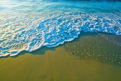 La mer bleue ondule sur le sable Photos libres de droits