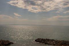 La mer de Bibione, Vénétie, Italie, avec une réflexion d'éblouissement et des nuages dans le ciel couvrant les rayons du ` s du s photographie stock