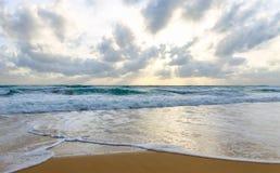 La mer de intersection ondule dans le sable pendant le coucher du soleil sur le rivage d'une île solitaire Photo stock