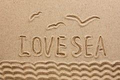 La mer de mot écrite sur le sable Images stock