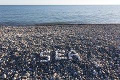 La mer de signe faite à partir des cailloux blancs Image stock