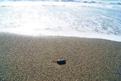 La mer et la pierre noire dans le sable images libres de droits