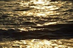 La mer légère ondule au coucher du soleil Photo stock