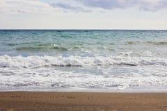 La mer Méditerranée d'hiver orageux et vident la plage sablonneuse Image libre de droits