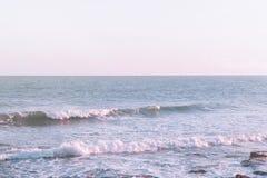 La mer ondulée mousseuse ondule le roulement à l'horizon pourpre de couleur en pastel de roses de Cliffy Shore Light Blue Water B Image libre de droits