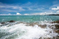La mer ondule la ligne de mèche roche d'impact sur la plage sous le ciel bleu Images stock