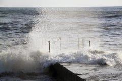 La mer ondule la rupture sur un brise-lames avec la mousse et les pulvérisateurs de mer Photos stock