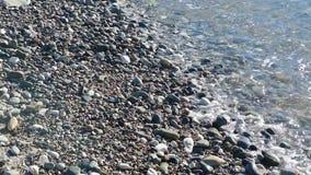 La mer ondule sur des cailloux