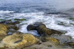 La mer ondule sur des pierres Images stock