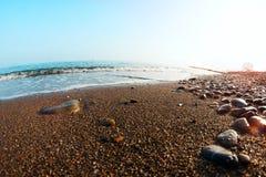La mer ondule sur la plage avec des rayons de coucher du soleil Photographie stock libre de droits