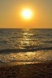 La mer ondule sur la plage de bardeau au coucher du soleil Photo libre de droits