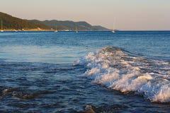 La mer ondule sur un rivage montagneux de fond avec la forêt photos stock