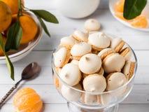 La meringue de biscuits en mandarines d'un vase en verre avec le vert part dans un plat sur le fond blanc Images libres de droits
