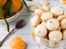 La meringue de biscuits en mandarines d'un vase en verre avec le vert part dans un plat sur le fond blanc Photographie stock libre de droits